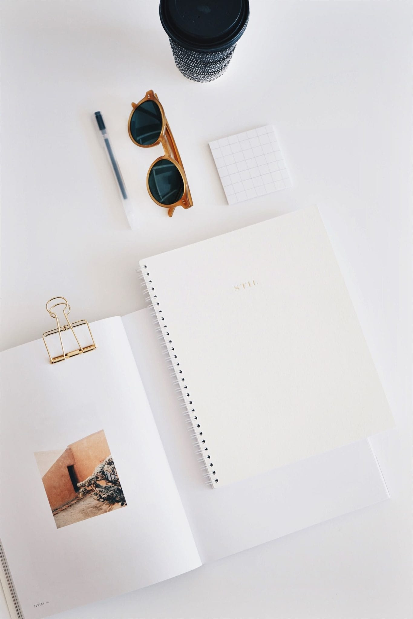 journal flat lay with sunglasses and coffee cup